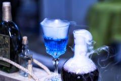 Den blåa rökflaskan som innehåller häxor, bryggar, manapåfyllning royaltyfri fotografi