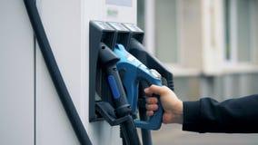Den blåa urladdningsdysan sätts tillbaka in i ställe i en elektrisk läggande tillbaka station lager videofilmer