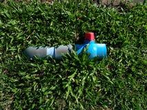 Den blåa vattenkranen på grönt gräs Royaltyfri Fotografi