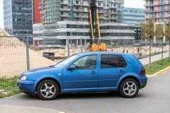Den blåa Volkswagen Golf droppen parkerade nära konstruktionsplats den Riga Arkivfoto