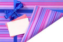 Den blåa gåvabandpilbågen på randigt inpackningspapper, hörn vek öppet för att avslöja vitt kopieringsutrymme inom Royaltyfri Bild