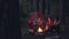 Den blandras- gruppen av vänfotvandrare spelar gitarren, sjunger och skrattar runt om lägereld i aftonen arkivfilmer