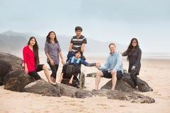 Den blandras- sakkunniga behöver familjen som sitter på stort, vaggar längs stranden royaltyfri foto