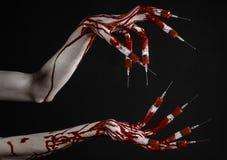 Den blodiga handen med injektionssprutan på fingrarna, tåinjektionssprutor, hand spolar ren, den förfärliga blodiga handen, det h Royaltyfria Bilder