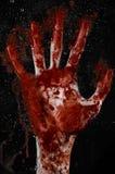 Den blodiga handen på det våta exponeringsglaset, det blodiga fönstret, en avtryck av blodiga händer, levande död, demon, mördare Arkivfoto