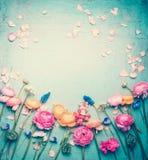 Den blom- ramen med älskvärda blommor och kronblad, retro pastell tonade på tappningturkosbakgrund