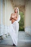 Den blonda ängeln med ljus vit påskyndar, och vit skyler att posera som är utomhus- Royaltyfria Foton
