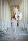 Den blonda ängeln med ljus vit påskyndar, och vit skyler att posera som är utomhus- Royaltyfri Foto