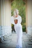 Den blonda ängeln med ljus vit påskyndar, och vit skyler att posera som är utomhus- Royaltyfri Fotografi