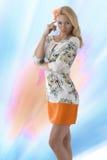 Den blonda bekläda klänningen med blom- mönstrar abd fingrar nära ten fotografering för bildbyråer