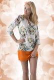 Den blonda bekläda klänningen med blom- mönstrar och räcker på höften Arkivbilder