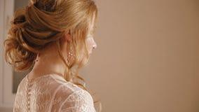 Den blonda bruden i en bröllopsklänning med blommor som poserar för kameran arkivfilmer