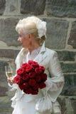 Den blonda bruden med den brud- påsen och de röda rosorna i hennes hand kopplar av med ett exponeringsglas av champagne, når han  arkivbilder