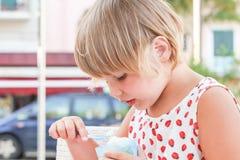 Den blonda caucasianen behandla som ett barn flickan äter den djupfrysta yoghurten Royaltyfri Fotografi