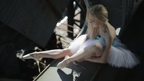 Den blonda dansaren i en vit ballerinakjol sitter på kanten av stock video