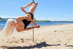 Den blonda dansaren utför akrobatiskt på pol Arkivbilder