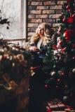 Den blonda flickan drömmer om en julgran royaltyfri foto