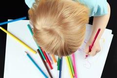 Den blonda flickan drar vid blyertspennan Arkivbilder