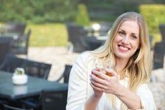 Den blonda flickan dricker Tea på cafen Royaltyfri Fotografi