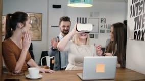 Den blonda flickan försöker app för exponeringsglas för VR-hjälmvirtuell verklighet hennes vänner och kollegor som stöttar henne  Royaltyfria Bilder