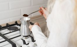 Den blonda flickan faller sovande malt kaffe i turk arkivbild