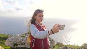 Den blonda flickan gör selfie på bakgrunden av att förbluffa naturen, vaggar, havet, grönska Den långhåriga tonåriga flickan ler  lager videofilmer