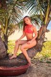 den blonda flickan i bikini sitter gömma i handflatan på blickar ler framåtriktat Arkivfoton