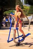 Den blonda flickan i bikini utbildar på gradvist parkerar in nära stranden Royaltyfri Foto