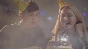 Den blonda flickan i födelsedaghatt som ut blåser stearinljus på kakan, den unga mannen som nära sitter Kvinnan har födelsedag stock video