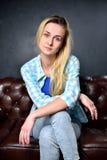 Den blonda flickan i jeans sitter på lädersoffan Arkivfoton