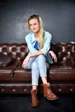 Den blonda flickan i jeans sitter på lädersoffan Royaltyfri Foto