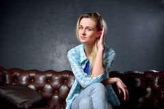 Den blonda flickan i jeans sitter på lädersoffan Arkivbilder