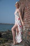 den blonda flickan klädde på stranden nära väggen och stenarna Fotografering för Bildbyråer