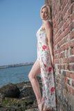 den blonda flickan klädde på stranden nära väggen och stenarna Royaltyfri Foto