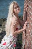 den blonda flickan klädde på stranden nära väggen och stenarna Royaltyfria Bilder