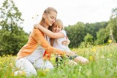 Den blonda flickan kramar lyckligt mamman fotografering för bildbyråer