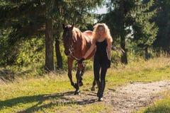 Den blonda flickan leder hästen vid tömmarna Royaltyfri Foto