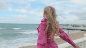Den blonda flickan lyfter henne armar upp på stranden lager videofilmer