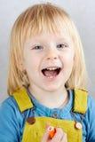 Den blonda flickan med den öppna munnen rymmer en filtpenna Royaltyfria Bilder