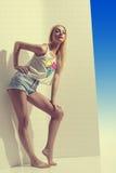 Den blonda flickan med denim kortsluter oavkortad längd Royaltyfri Foto