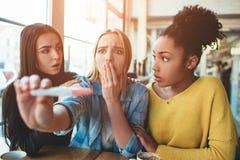 Den blonda flickan rymmer en graviditetstest som visar till hennes positiva resultat av provet som hon ser dissapointed, ledset o arkivfoton