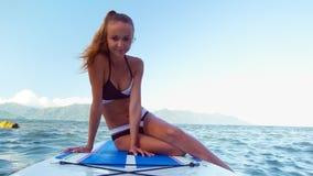 Den blonda flickan sätter fot in i vatten från skovelbräde i havet lager videofilmer
