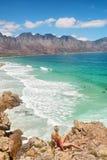 Den blonda flickan ser den majestätiska stranden arkivfoto