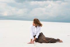 Den blonda flickan sitter bland de gränslösa sanderna arkivfoto