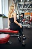 Den blonda flickan sitter i idrottshallen Hon bär mörka flåsanden, den svarta T-tröja och svarta gymnastikskor Hennes högra ben ä Royaltyfri Bild