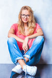 Den blonda flickan som bär exponeringsglas, poserar, medan sitta på golvet Royaltyfri Bild