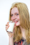 Den blonda flickan som dricker exponeringsglas av, mjölkar Arkivfoto