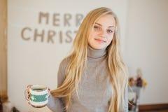 Den blonda flickan som dricker hennes kaffe, äter kakor och läste en bok Arkivfoto