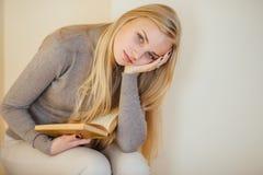 Den blonda flickan som dricker hennes kaffe, äter kakor och läste en bok Arkivfoton