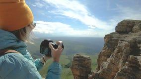 Den blonda flickan som fotografen i locket tar ett foto på hennes digitala kamera med en bakgrund av, vaggar i Kaukasuset stock video